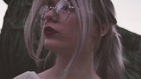 Belle jeune fille en verres posant pour le portrait dans les lumières clignotantes banque de vidéos