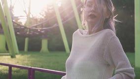 Belle jeune fille en verres posant près des montagnes russes dans le faisceau lumineux du soleil banque de vidéos