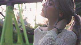 Belle jeune fille en verres posant près des montagnes russes dans le rayon lumineux du soleil banque de vidéos