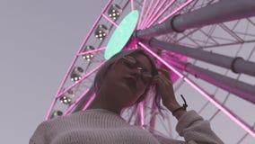Belle jeune fille en verres posant sous la roue de ferris avec les lumières clignotantes clips vidéos