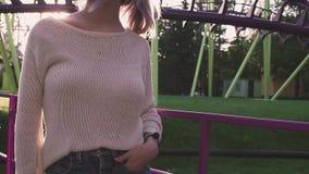 Belle jeune fille en verres tenant les montagnes russes proches dans le rayon lumineux du soleil banque de vidéos