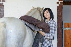 Belle jeune fille et cheval blanc dans l'écurie Image stock