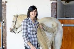 Belle jeune fille et cheval blanc dans l'écurie Photographie stock libre de droits