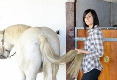 Belle jeune fille et cheval blanc dans l'écurie Photo stock