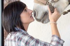 Belle jeune fille et cheval blanc dans l'écurie Photographie stock