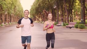 Belle jeune fille et hommes formant des courses en parc, mouvement lent clips vidéos
