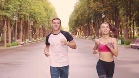 Belle jeune fille et hommes formant des courses en parc, mouvement lent banque de vidéos