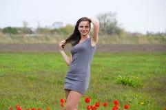 Belle jeune fille féerique dans un domaine parmi les fleurs des tulipes Portrait d'une fille sur un fond des fleurs rouges et d'u Photos libres de droits