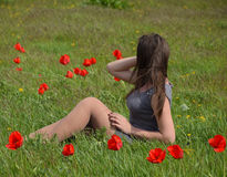 Belle jeune fille féerique dans un domaine parmi les fleurs des tulipes Portrait d'une fille sur un fond des fleurs rouges et d'u Photo libre de droits