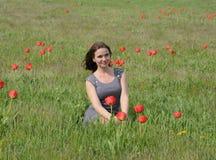 Belle jeune fille féerique dans un domaine parmi les fleurs des tulipes Portrait d'une fille sur un fond des fleurs rouges et d'u Photo stock