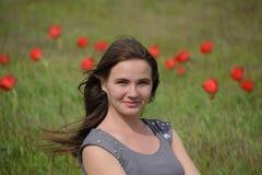 Belle jeune fille féerique dans un domaine parmi les fleurs des tulipes Portrait d'une fille sur un fond des fleurs rouges et d'u Image libre de droits