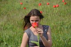 Belle jeune fille féerique dans un domaine parmi les fleurs des tulipes Portrait d'une fille sur un fond des fleurs rouges et d'u Image stock