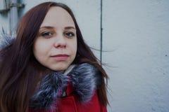 Belle jeune fille heureuse dans une veste rouge posant dehors un jour nuageux images stock