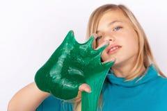 Belle jeune fille jouant avec la boue verte photos stock