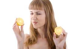 Belle jeune fille jugeant un citron aigre d'isolement Image libre de droits