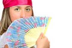 Belle jeune fille ondulant un ventilateur Images stock