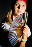 Belle jeune fille ondulant un ventilateur Image stock