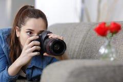 Belle jeune fille prenant à photo deux roses à la maison Photographie stock libre de droits