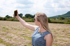 Belle jeune fille prenant un selfie dans la campagne photos libres de droits
