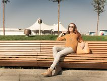 Belle jeune fille reposant sur un banc sur des whis chauds d'un jour d'été un sac Photo stock