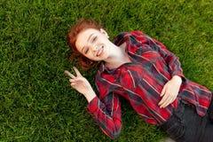 Belle jeune fille rousse d'étudiant avec des taches de rousseur se trouvant sur elle de retour sur la vue d'herbe et de pelouse d photos stock