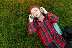 Belle jeune fille rousse d'étudiant avec des taches de rousseur se trouvant sur elle de retour sur la vue d'herbe et de pelouse d photo libre de droits