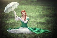 Belle jeune fille rousse dans une robe verte médiévale avec un parapluie se reposant sur l'herbe Images libres de droits