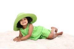 Belle jeune fille s'étendant dans le sable Photographie stock libre de droits