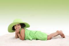 Belle jeune fille s'étendant dans le sable utilisant le grand chapeau vert images stock