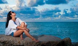 Belle jeune fille s'asseyant par l'océan appréciant le coucher du soleil Photos libres de droits