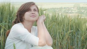 Belle jeune fille s'asseyant parmi les épillets verts grands du blé dans le domaine Jeune femme heureuse appréciant l'été, harmon banque de vidéos