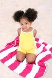 Belle jeune fille s'asseyant sur l'essuie-main de plage dans le sable Images libres de droits