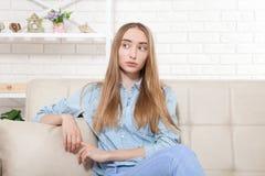 Belle jeune fille s'asseyant sur le fond de sofa à la maison Copiez l'espace et raillez  Dépression d'adolescent Femme triste Photos libres de droits