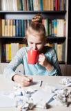 Belle jeune fille s'asseyant sur le lieu de travail avec chiffonner la feuille Photographie stock