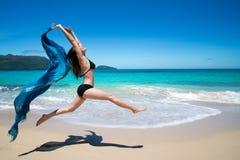 Belle jeune fille sautant avec onduler le cap bleu, écharpe, sur la plage tropicale images libres de droits