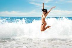 Belle jeune fille sautant sur la mer Photos stock