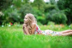 Belle jeune fille se trouvant sur l'herbe Photos stock