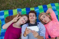Belle jeune fille se trouvant sur la couverture et prenant le selfie Photographie stock libre de droits