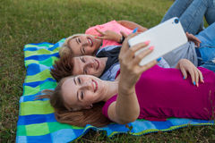 Belle jeune fille se trouvant sur la couverture et prenant le selfie Photographie stock