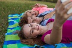 Belle jeune fille se trouvant sur la couverture et prenant le selfie Images libres de droits