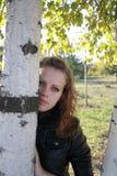 Belle jeune fille seule près d'un bouleau Photographie stock libre de droits