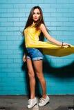 Belle jeune fille sexy de hippie posant et souriant près du fond bleu urbain de mur dans la robe jaune, shorts, chemise Images libres de droits