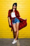 Belle jeune fille sexy de hippie posant et souriant près du fond jaune urbain de mur dans des lunettes de soleil Photos libres de droits