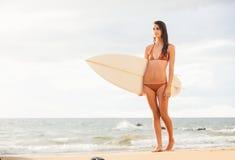Belle jeune fille sexy de surfer dans le bikini sur la plage au sunse Image libre de droits