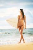 Belle jeune fille sexy de surfer dans le bikini sur la plage au sunse Photographie stock libre de droits