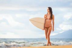 Belle jeune fille sexy de surfer dans le bikini sur la plage au sunse Photographie stock