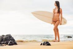 Belle jeune fille sexy de surfer dans le bikini sur la plage au sunse Photos libres de droits