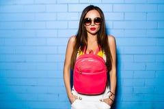 Belle jeune fille sexy posant et souriant près du fond bleu de mur dans le maillot de bain jaune, lunettes de soleil, sac à dos r Photo stock