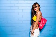 Belle jeune fille sexy posant et souriant près du fond bleu de mur dans le maillot de bain jaune, lunettes de soleil, sac à dos r Images stock