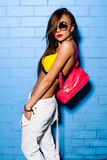 Belle jeune fille sexy posant et souriant près du fond bleu de mur dans le maillot de bain jaune, lunettes de soleil, sac à dos r Photographie stock